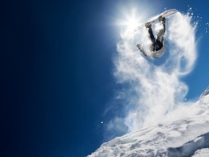 Sport Nägele - Snowboarder making high jump in clear blue sky